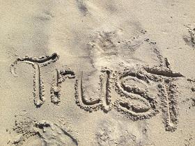 'Trust' written in sand