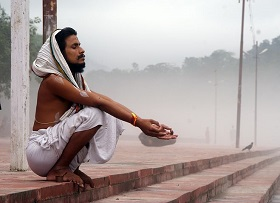 A man reciting mantras at the bank of a river